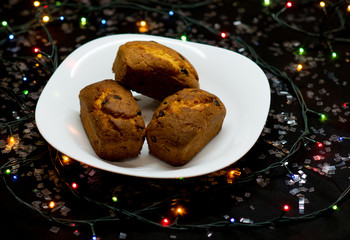 Festive cupcakes with raisins on a black background.