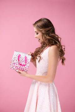 Excited woman opening a gift in the studio shot
