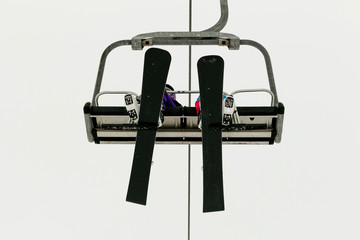 two snowboarders ride chairlift background in sky