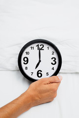man grabbing a clock at seven in bed