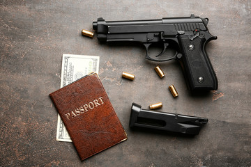 Pistol, passport and money on wooden background