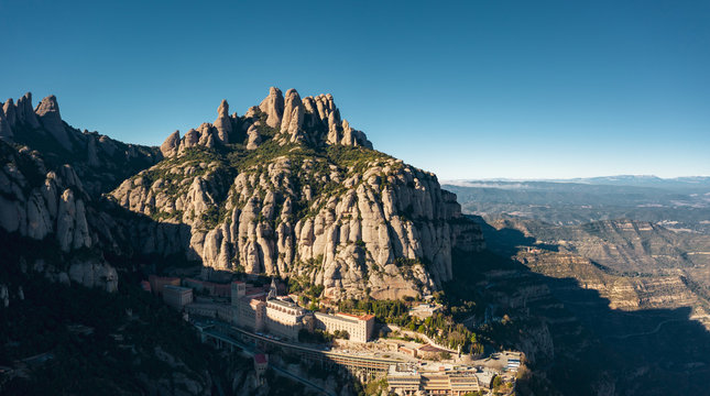 Aerial; drone view of multi-peaked mountain range; site of Benedictine abbey, Santa Maria de Montserrat; highest summit of Montserrat is Sant Jeroni; the location of the Holy Grail in Arthurian myth