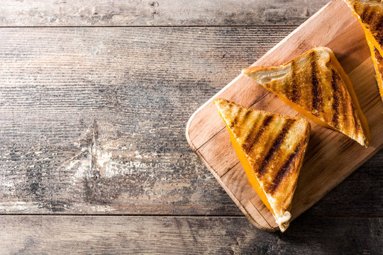 Grilled cheese sandwich on wooden table. Top view. Copyspace