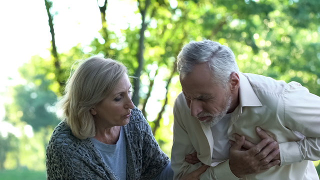 Old man having sudden heart attack during walk in park, wife helping him, care