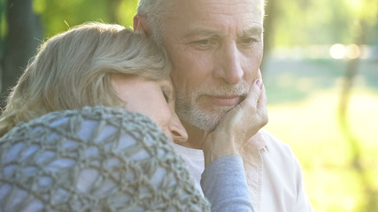 Caring woman in her 50s tenderly touching husband face, relationship and love
