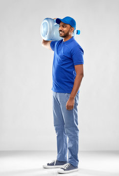 service and people concept - happy indian delivery man with water barrel in blue uniform over grey background
