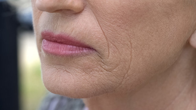 Wrinkled face of pensioner female, anti-age cream, skincare and cosmetology