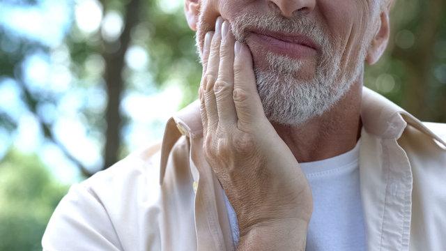 Senior man having problem with teeth, social program of dental prosthetics