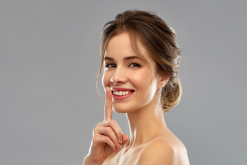 beauty, secret and people concept - beautiful smiling woman making hush gesture over grey background