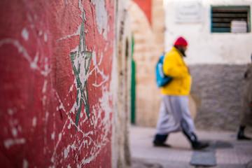 Green star flag of Morocco on street wall in Essaouira Medina