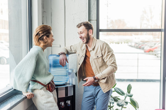 casual businessman and woman talking and laughing in loft office