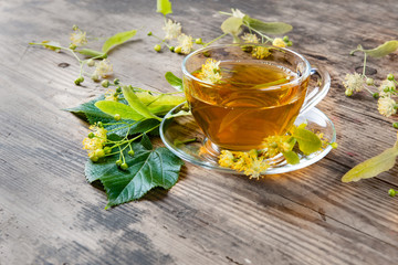 Cup of green tea and linden on wooden background