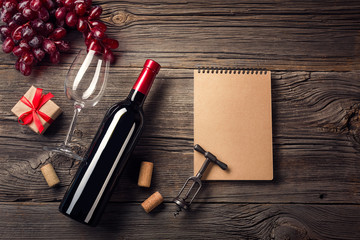 Holiday Dinner setting with red wine and gift on rustic wood in flat lay view.