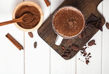 Fotobehang - Hot chocolate in the cup, cocoa beans and powder on the white wooden table