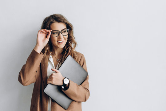 Beautiful business woman in a glasses with smile and a laptop in her hands in the office near a white wall with blank space for text
