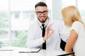 Male doctor is talking with female patient in hospital office. Healthcare and medical service.