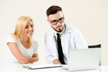 Male doctor talks to female patient in hospital office while looking at the patients health data on laptop computer on the table. Healthcare and medical service.