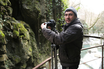 videographer shoots video from a tripod in a forest in the mountains