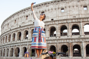 Beautiful young woman taking selfie pictures with smartphone standing in front of colosseum in Rome at sunset.