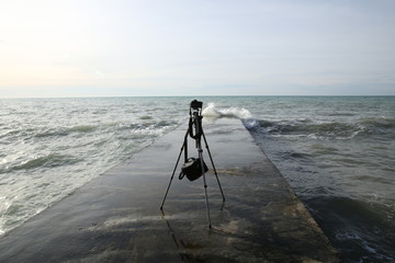 tripod with a camera is standing on the breakwater in the sea without a photographer