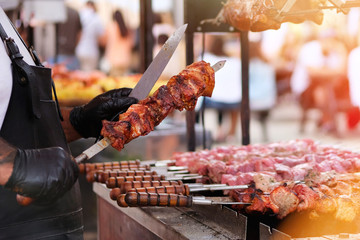 Chef frying meat on grill. Cook in black apron fries meat on fire. Barbecue in open air. Bright sunlight bokeh