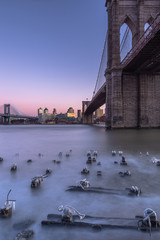 Brooklyn and manhattan bridge at sunset view from frozen pier with long exposure