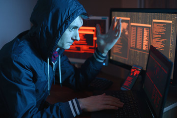 Male hacker celebrates success with a hand gesture. A successful attempt at system hacking and data theft