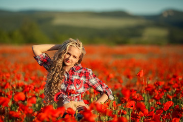 Young blonde in a red shirt in the poppy flower field.