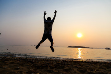 Silhouette behind of cheerful man with arms raised on the beach at sunset.
