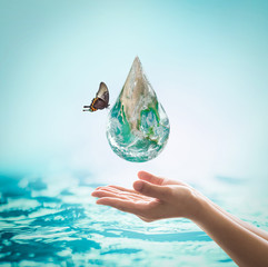 World ocean day,, saving water campaign, sustainable ecological ecosystems concept with green earth on woman's hands on blue sea background : Element of this image furnished by NASA .
