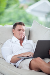 portrait of young man on sofa with laptop in summer house environment