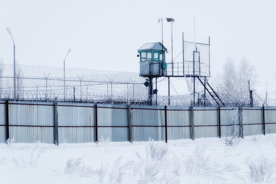 Prison guarding tower, fence with barbed wire