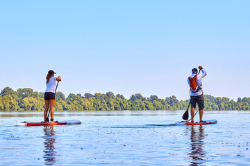 Athletic teen girl and man on the SUP (stand up paddle board, paddleboard) paddling in Danube river at summer morning