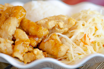 Chinese food, rice with fried chicken in soya sauce and vegetables, cabbage and carrots in a white plate, close up