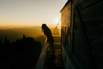 Person standing on balcony during sunset