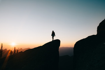 silhouette of woman on top of the mountain at sunset