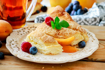 Delicious puff pastry cakes filled with cheese and fruits.