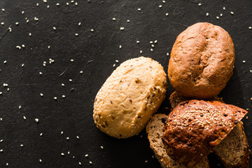Home bakery. Bread recipe variety. Assorted pieces with sesame seeds on black background.