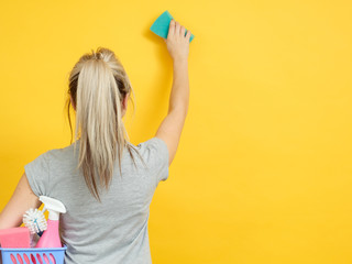 Home cleaning. Safe and efficient supplies. Woman with basket set raised hand wiping. Copy space on yellow background.