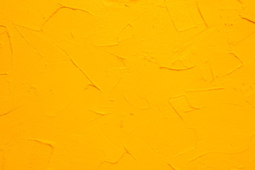 Yellow textured wall. Decorative plastering close-up photo. Surface with stucco daub