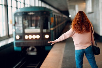 Positive redhead young female stops subway train