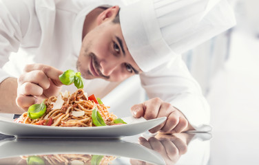 Chef in restaurant kitchen prepares and decorates meal with hands.Cook preparing spaghetti bolognese