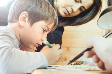 Child painting a picture at home with his parents. Couple assisting your son in drawing a picture.
