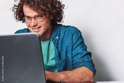Young Happy Businessman With Curly Hair Working On His