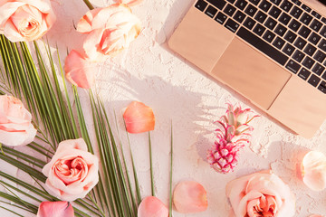 Flat lay of tropical workspace mockup with modern laptop, palm monstera leaves, pink flowers, exotic pineapple and petals on pastel background. top view