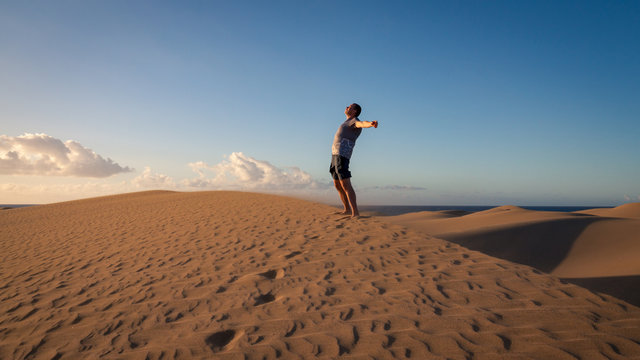 Man is relax and meditation on sand dunes in Maspalomas.