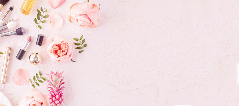 Makeup products and make-up brush with pink flowers on pastel background. Panoramic banner with copy space for text. Luxury beauty.