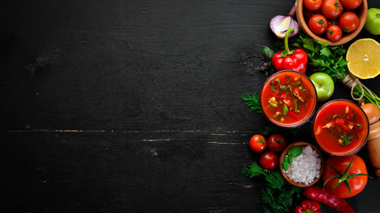 Gazpacho Soup in Glas. Tomato soup with onion, paprika and parsley. Italian cuisine. Top view. On a black background. Free space for text.