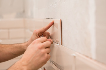 Stylish trendy beige ceramic tiles with chamfer on the kitchen wall. Hands tiler in the process of laying white rectangular tiles on the bathroom wall. Repair of apartments and bathrooms.ceramic tile