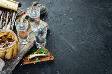 Sandwich with sprats and vodka. Sprat in oil. On a black background. top view. Free copy space.